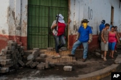 Sandinista militias stand guard at a torn-down barricade after police and pro-government militias stormed the Monimbo neighborhood of Masaya, Nicaragua, July 17, 2018.
