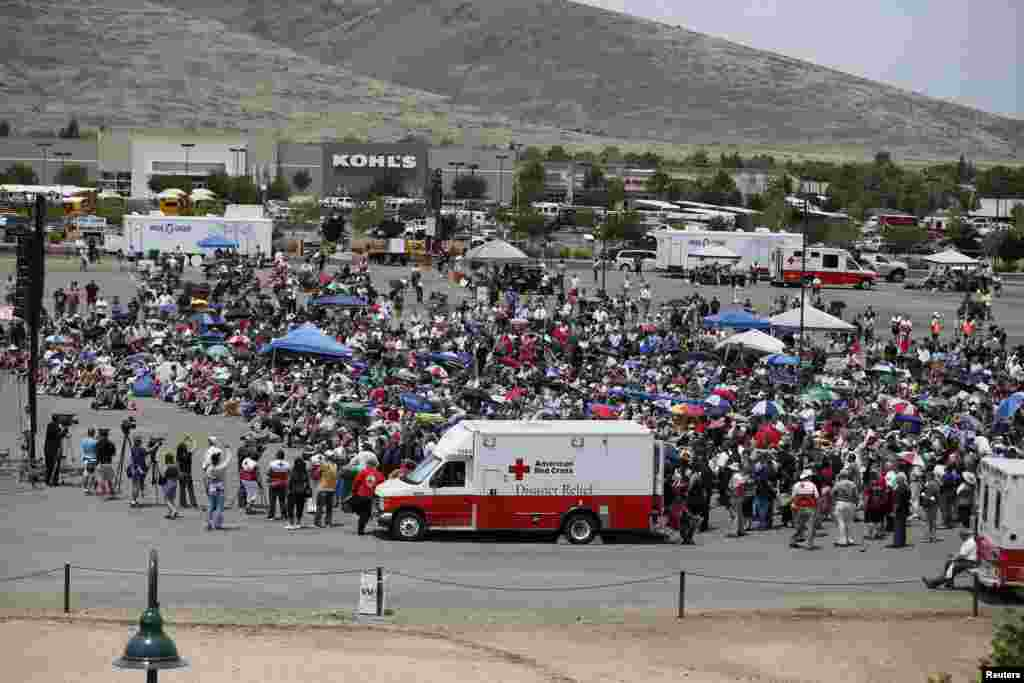 People watch a memorial service for the fallen members of the Granite Mountain Hotshots on a big screen outside the memorial arena, in Prescott Valley, Arizona, July 9, 2013.