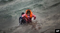 A man carries a child as they try to reach a shore after falling into the sea while disembarking from a dinghy on which they crossed a part of the Aegean sea with other refugees and migrants, from Turkey to the Greek island of Lesbos, Jan. 3, 2016.