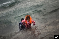 FILE - A man carries a child as they try to reach a shore after falling into the sea while disembarking from a dinghy on which they crossed a part of the Aegean sea with other refugees and migrants, from Turkey to the Greek island of Lesbos, Jan. 3, 2016.