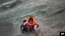 Seorang pria menggendong anaknya mencapai pantai setelah jatuh ke laut dari perahu karet yang mereka gunakan untuk menyeberangi Laut Aegea beresama para pengungsi dan migran lainnya, dari Turki ke pulau Lesbos, Yunani, Minggu, 3 Januari 2016.