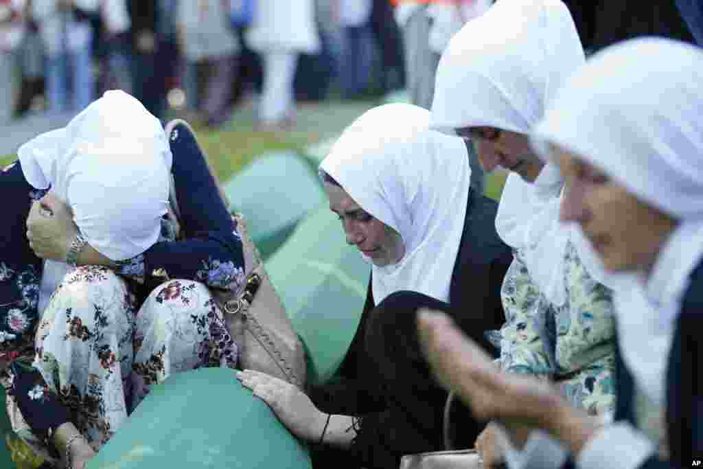 Bosnian Muslim women react near the coffin of one of the 35 identified victims of the 1995 massacre, at the memorial center of Potocari near Srebrenica, 150 kilometers northeast of Sarajevo. Thousands of Bosnian Muslims have gathered in Srebrenica on the 23rd anniversary of Europe's worst massacre since World War II to hold prayers and attend the funeral for 35 recently identified victims.