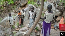 Sudanese children displaced from their homes in the rebel stronghold of Kauda take shelter in the hills surrounding the town in the Nuba mountains as they flee with their families from government bombardment, June 30, 2011