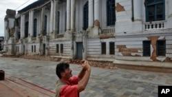 Du khách chụp ảnh một tòa nhà bị hư hại gần Basantapur Durbar Square ở Kathmandu, Nepal, ngày 15/6/2015.