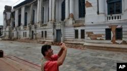 Tourist photographs a damaged building near Basantapur Durbar Square in Kathmandu, Nepal, June 15, 2015.