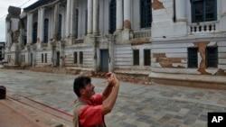 Turis memotret gedung rusak dekat Alun-alun Basantapur Durbar di Kathmandu, Nepal (15/6). (AP/Niranjan Shrestha)