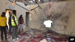 """People inspect a damaged mosque following an explosion in Maiduguri, Nigeria, Oct. 23, 2015. The United States condemned """"horrific and indiscriminate attacks"""" in northeastern Nigeria carried out by the Islamist militant group Boko Haram."""