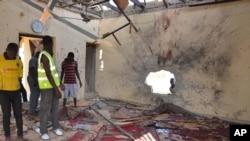 Warga memeriksa sebuah masjid yang rusak akibat ledakan di Maiduguri, Nigeria, 23 Oktober 2015. Boko Haram dicurigai berada di balik pengeboman tersebut. (AP Photo/Jossy Ola)