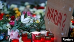 "Plakat bertuliskan ""Mengapa?"" di pasar Natal di Berlin, Jerman (20/12). (Reuters/Hannibal Hanschke)"