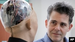 FILE - In this Sept. 28, 2017, photo, David Hanson, the founder of Hanson Robotics, talks with his company's flagship robot Sophia, a lifelike robot powered by artificial intelligence in Hong Kong.