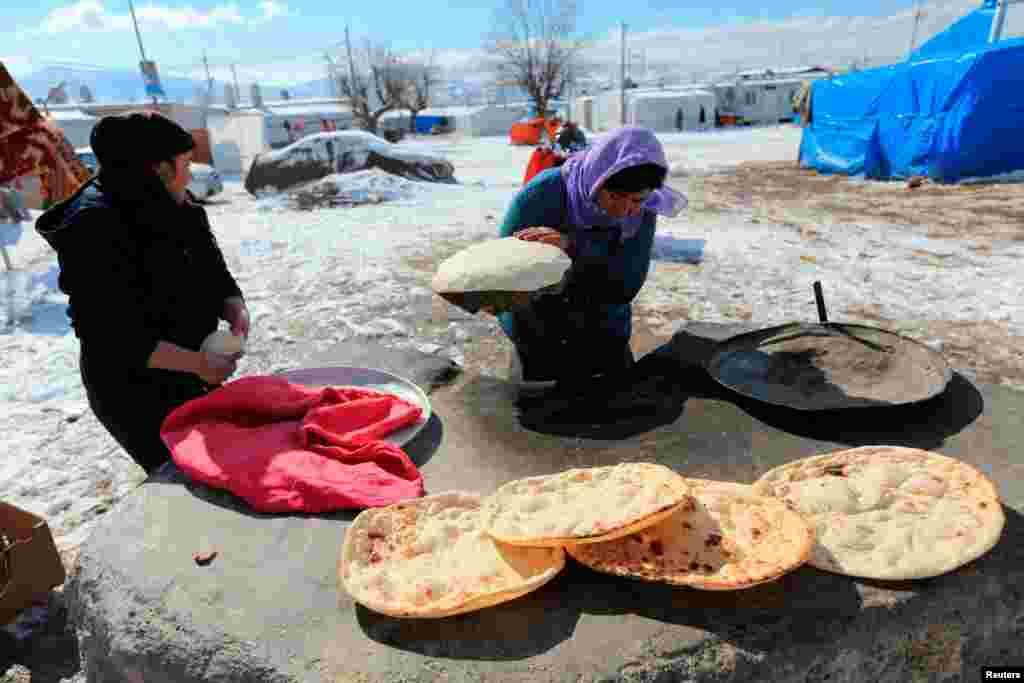 چند زن آواره عراقی در یک اردوگاهی در شهر دهوک عراق نان درست میکنند.