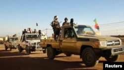 Soldiers from the Tuareg rebel group MNLA drive in a convoy of pickup trucks in the northeastern town of Kidal, Mali, Feb. 4, 2013.