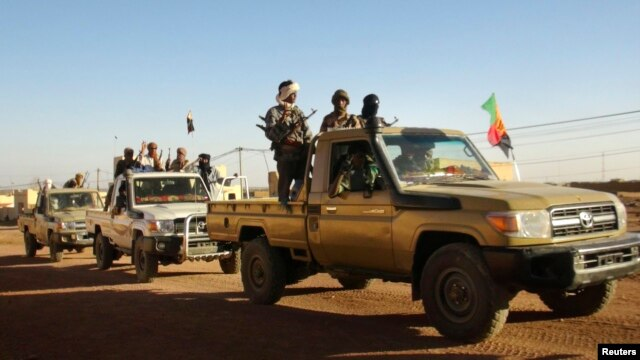 FILE - Soldiers from the Tuareg rebel group MNLA drive in a convoy of pickup trucks in the northeastern town of Kidal, Mali, February 4, 2013.