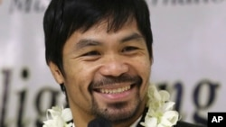 In this April 14, 2016 file photo - Filipino boxer and Congressman Manny Pacquiao smiles as he answers questions from reporters upon his arrival at the Ninoy Aquino International Airport in suburban Pasay city, south of Manila, Philippines, after beating American Timothy Bradley during their WBO welterweight title boxing match in Las Vegas.