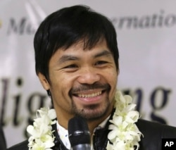 In this April 14, 2016 file photo - Filipino boxer and Congressman Manny Pacquiao smiles as he answers questions from reporters upon his arrival at the Ninoy Aquino International Airport in suburban Pasay city, south of Manila, Philippines, after beating