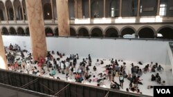 "Visitors gather at the National Building Museum exhibit, ""The Beach,"" in Washington, D.C. (W. Wisniewski/VOA)"