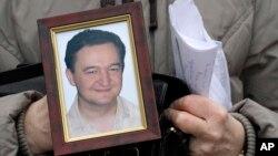 Nataliya Magnitskaya membawa foto puteranya, pengacara Sergei Magnitsky, yang tewas dalam tahanan di Moskow (foto: dok). AS mengumumkan sanksi bagi pejabat Rusia yang terlibat kematian Magnitsky.