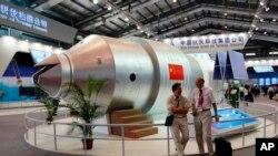 Arhiva - Na ovoj fotografiji od 16. novembra 2010, posjetioci stoje ispred modela kineske Tinagong-1 svemirske stanice na Osmoj kineskoj međunarodnoj i svemirskoj izložbi u Zuhaiu, u južnoj kineskoj Guangdong provinciji.