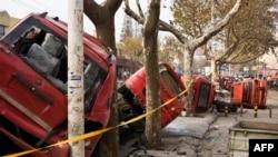 Kendaraan-kendaraan yang rusak terlihat di jalanan setelah sebuah pipa minyak meledak, menewaskan setidaknya 35 orang, membelah jalan dan membalikkan mobil-mobil di atasnya serta mengakibatkan kepulan asap hitam di atas kota Qingdao, Shandong, China.