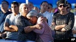 Bat-Galim Shaar (kanan) dan Iris Yifrah (tengah), para ibu dari dua diantara tiga remaja Israel yang diculik dan dibunuh di Tepi Barat berduka saat pemakaman putra-putra mereka di Modiin (1/7/2014). Hamas mengaku bahwa mereka berada di belakang penculikan itu yang bertujuan untuk memicu perang di Gaza.