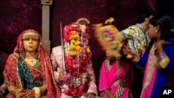 Vijay, 20, sits with his wife Preeti, 15, during mass marriage ceremony, Karachi, Nov. 12, 2011.