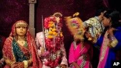 Vijay, 20, sits with his wife Preeti, 15, during mass marriage ceremony, Karachi, Nov. 12, 2011.