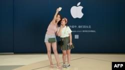 Khách hàng chụp ảnh tự sướng bên ngoài một cửa hàng Apple ở Bắc Kinh hôm 16/8.