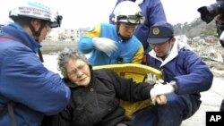 80-year-old Sumi Abe (C) is helped by emergency workers after being rescued from under the rubble in Ishinomaki City, Miyagi Prefecture, northern Japan, in this picture taken by Nikkei Shimbun on March 20 , 2011