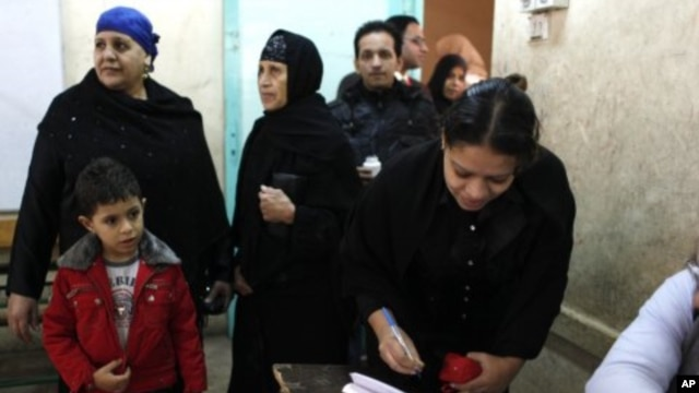 An Egyptian woman registers to vote while others are lining up at a polling center in Giza, Egypt, December 21, 2011.