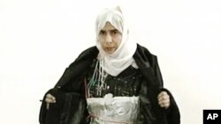 FILE - Iraqi Sajida Mubarek Atrous al-Rishawi opening her jacket and showing an explosive belt as she confesses on Jordanian state-run television to her failed bid to set off a bomb inside one of three Amman hotels targeted by al-Qaida in Jordan, Nov. 13, 2005.
