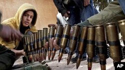 리비아 벵가지의 한 군사훈련기지에서 카다피에 저항하는 반군에 갓입대한 지원자들이 탄약정비를 돕고 있다.