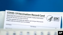 A vaccination record card is shown during a COVID-19 vaccination drive for Spring Branch Independent School District education workers, March 16, 2021, in Houston, Texas.