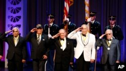 Members of the U.S. Army 65th Infantry Regiment, the Borinqueneers, salute during the singing of the National Anthem, after receiving their awards, during the Hispanic Heritage Awards, at the Warner Theater, Thursday, Sept. 18, 2014 in Washington.