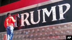 FILE - A worker removes letters from a Trump logo in Atlantic City, N.J.China has granted preliminary approval for 38 new Trump trademarks, fueling concerns about conflicts of interest and preferential treatment of the U.S. president.