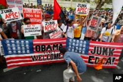 Protesters burn mock American flags during a rally outside of the US Embassy to protest alleged US military's involvement in the row between the Philippines and China on the disputed islands in the South China Sea, Thursday, in Manila, Philippines, Nov. 1