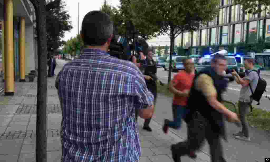 Armed police move past onlooking media responding to a shooting at Olympia Einkaufszentrum shopping center, July 22, 2016.