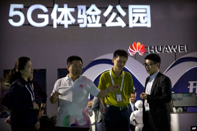 FILE - Visitors look at a display for 5G wireless technology from Chinese technology firm Huawei at the PT Expo in Beijing, Sept. 26, 2018.