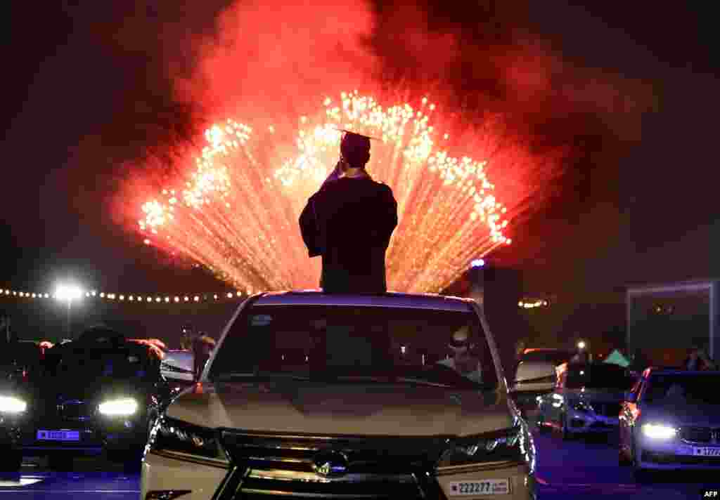 High school seniors of Bahrain Bayan School and their families watch fireworks at Bahrain International Circuit (BIC) in Sakhir race track, June 10, 2020, south of Manama following a graduation ceremony.