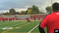 Dunbar High School Football Coach Craig Jefferies watches his team practice
