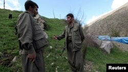 Kurdistan Workers Party (PKK) fighters talk to each other as they stand guard at the Qandil mountains near the Iraq-Turkish border in Sulaimaniya, 330 kilometers northeast of Baghdad, Iraq, March 24, 2013.