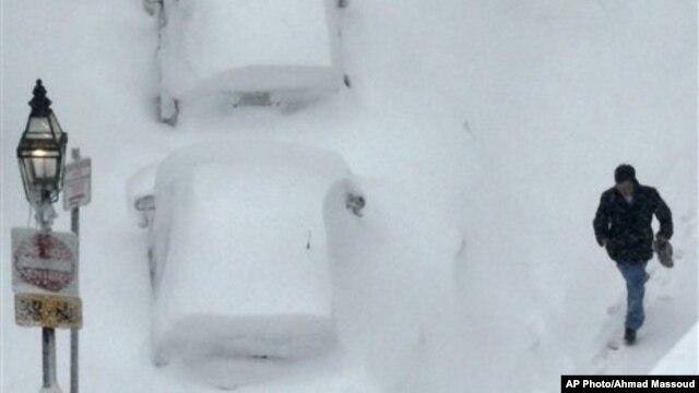 Seorang pria melewati salju yang menyelimuti mobil-mobil yang diparkir di pelataran parkir wilayah South End, Boston, Sabtu, 9 Februari 2013. Badai telah menghantam Boston dengan  salju yang mencapai sekitar dua kaki akhir pekan ini (AP Photo/Charles Krupa)