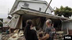 Maree (kiri), Jasmine (tengah) dan Norm Butcher memandangi rumah mereka di Christchurch, Selandia Baru, yang rubuh akibat gempa.