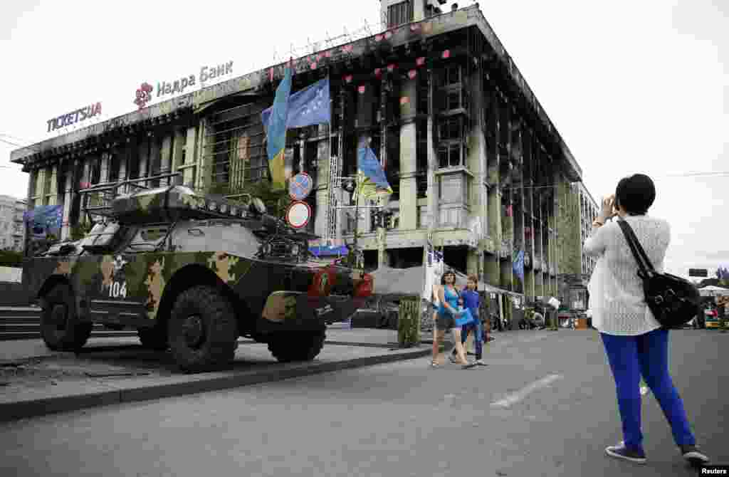 A woman takes a picture of an armoured vehicle in Independence Square, Kyiv, May 23, 2014.