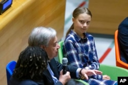Swedish environmental activist Greta Thunberg, right, listens to U.N. Secretary-General Antonio Guterres, left, during the Youth Climate Summit at United Nations headquarters, Saturday, Sept. 21, 2019.