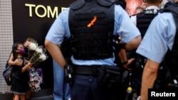 香港警察在街頭制止一對持花母女悼念一位刺傷警察後自殺身亡的男子。 (2021年7月2日)