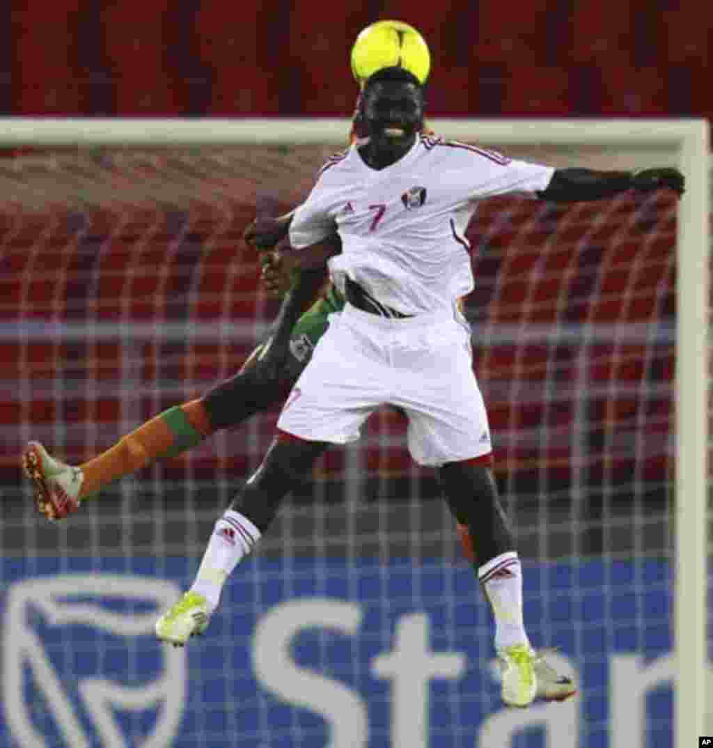 """Chisamba Lungu of Zambia fights for the ball with Ramadan Alagab of Sudan (front) during their African Nations Cup quarter-final soccer match at Estadio de Bata """"Bata Stadium"""", in Bata February 4, 2012."""