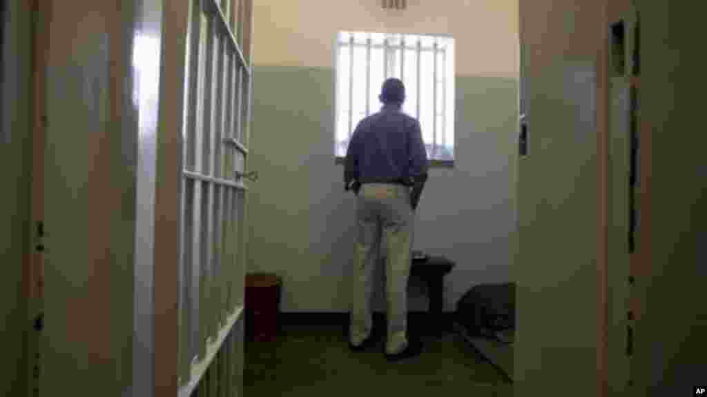 Barack Obama looks out from Mandela's former cell No. 5, on Robben Island, South Africa.