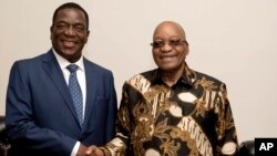 FILE: In this photo supplied by Government Communications and Information Services, (GCIS) former Vice-President of Zimbabwe, Emmerson Mnangagwa, left, shakes hands with South Africa President Jacob Zuma during a short visit, in Pretoria, South Africa.