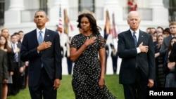 Dari kiri: Presiden AS Barack Obama, Ibu Negara Michelle Obama dan Wakil Presiden Joe Biden memimpin upacara peringatan 13 tahun tragedi serangan teroris 11 September, di Gedung Putih, Washington dengan mengheningkan cipta untuk menghormati para korban (11/9).
