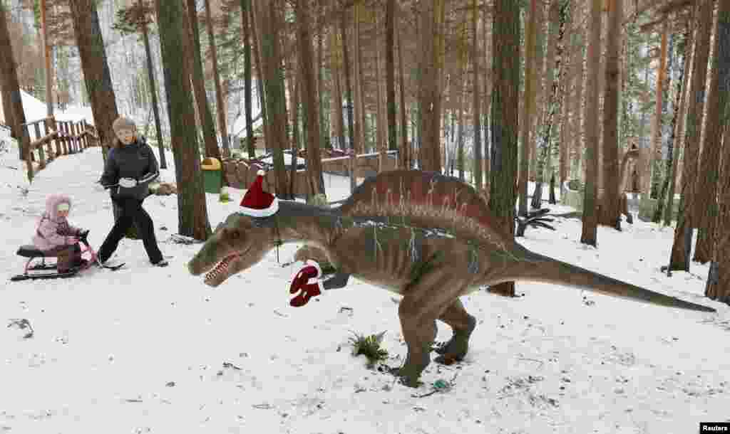 People walk past a model of a dinosaur, with Santa Claus hat and gloves on it, at the Dinosaurs Park located in the Taiga area at the Royev Ruchey zoo in the suburbs of Russia's Siberian city of Krasnoyarsk.